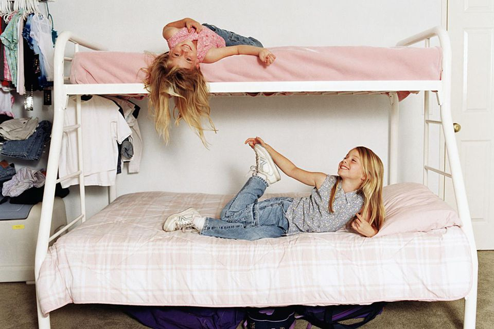 Twin sisters (5-7) lying on bunk beds