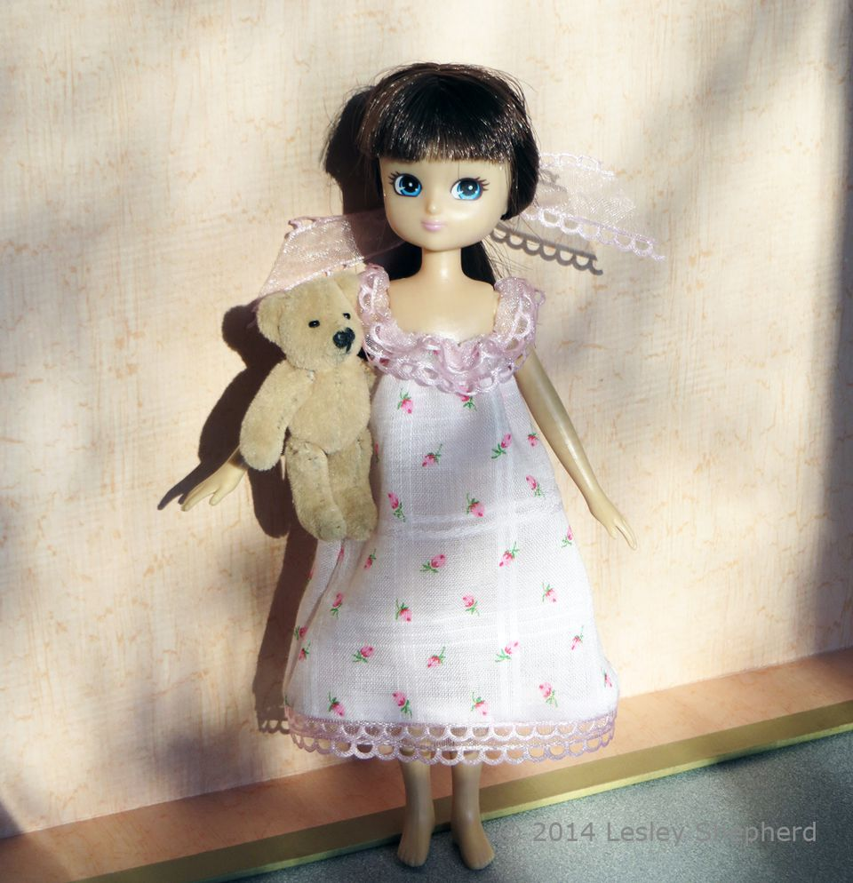 Lottie doll in a simple hand sewn nightdress with gathered ribbon trim.