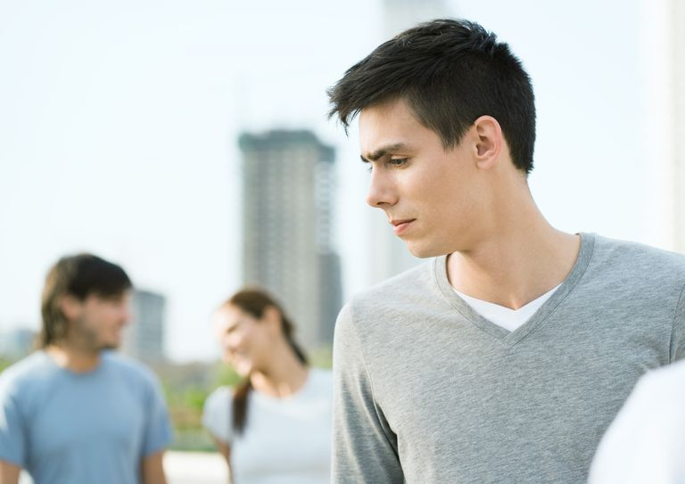 upset teen boy listening to friends talking