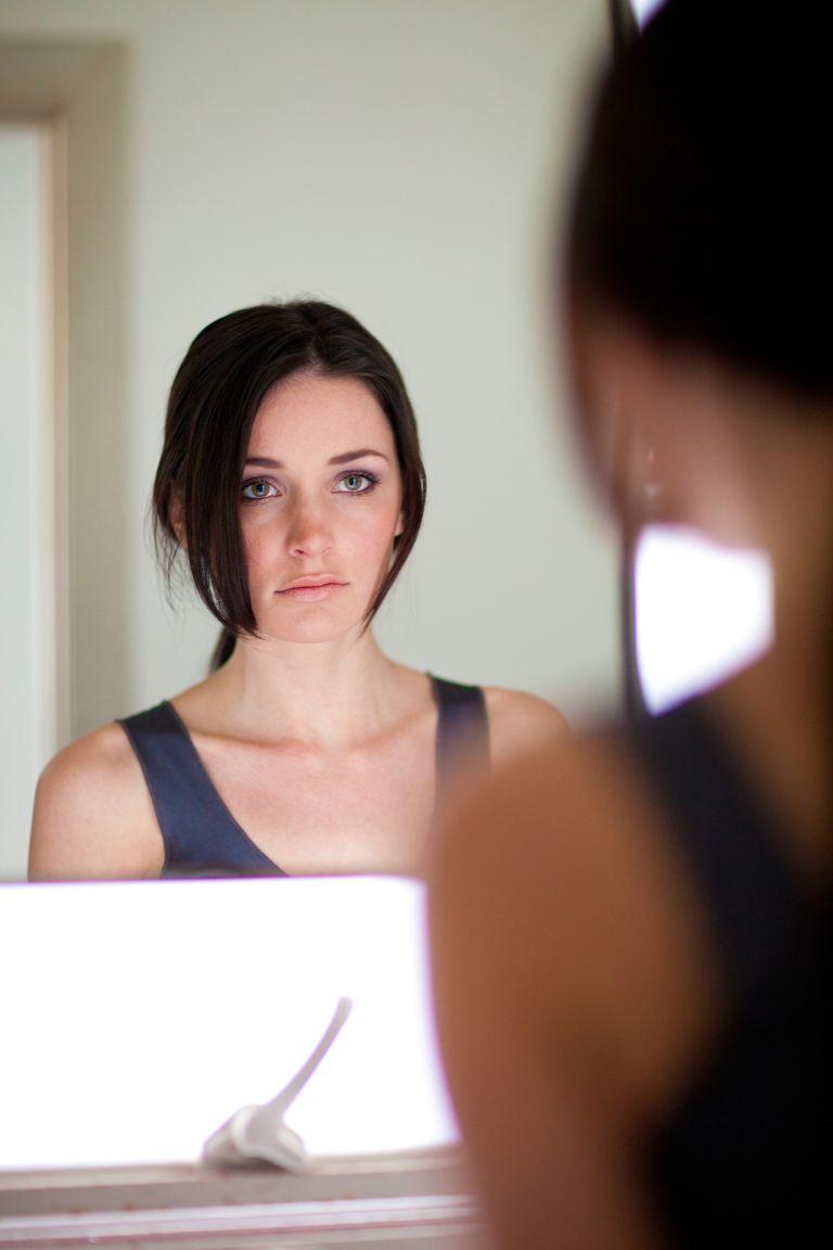 woman looking in mirror unhappy