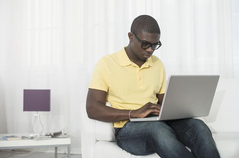 Young man with laptop computer in living room