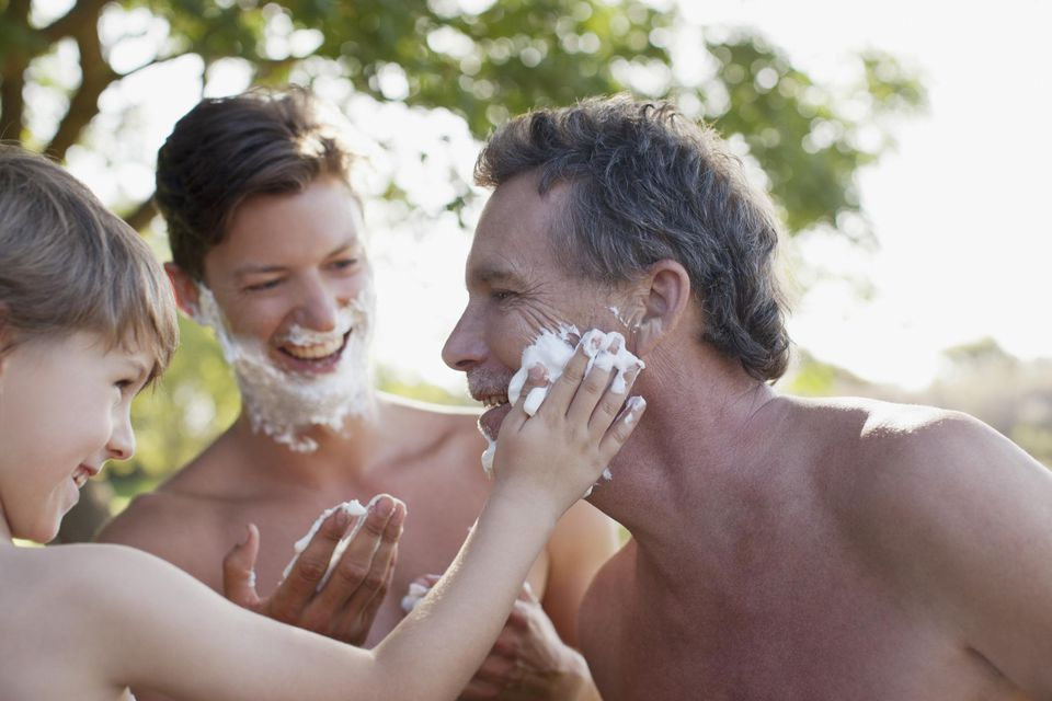 Multi-generation men applying shaving cream to faces
