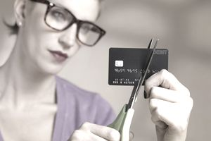 a woman cutting her credit card with scissors