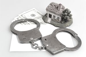Handcuffs, house figurine and currency on envelope