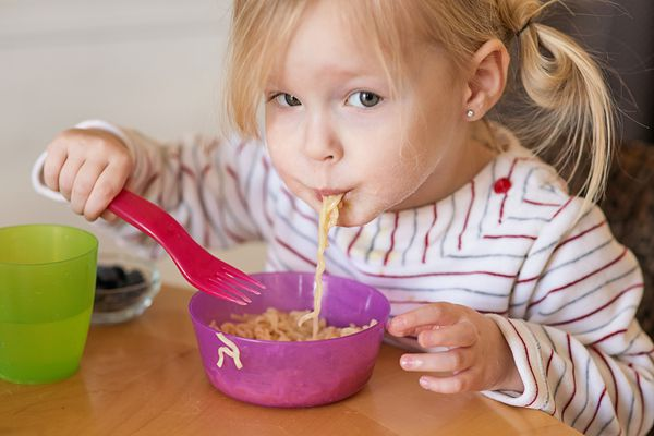 Toddler girl eating noodles from bowl