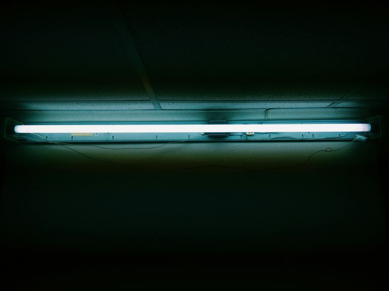 Fluorescent lights contain atoms that are excited, causing them to release energy that makes coatings in the light glow.