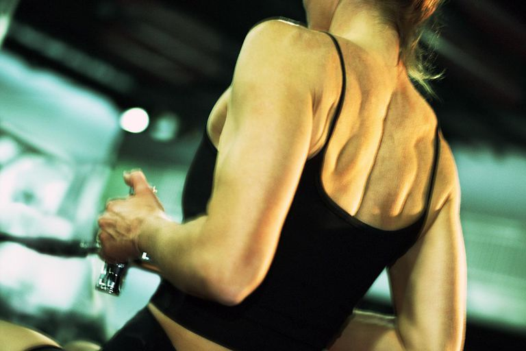 Woman using rowing weight machine in gym, rear view