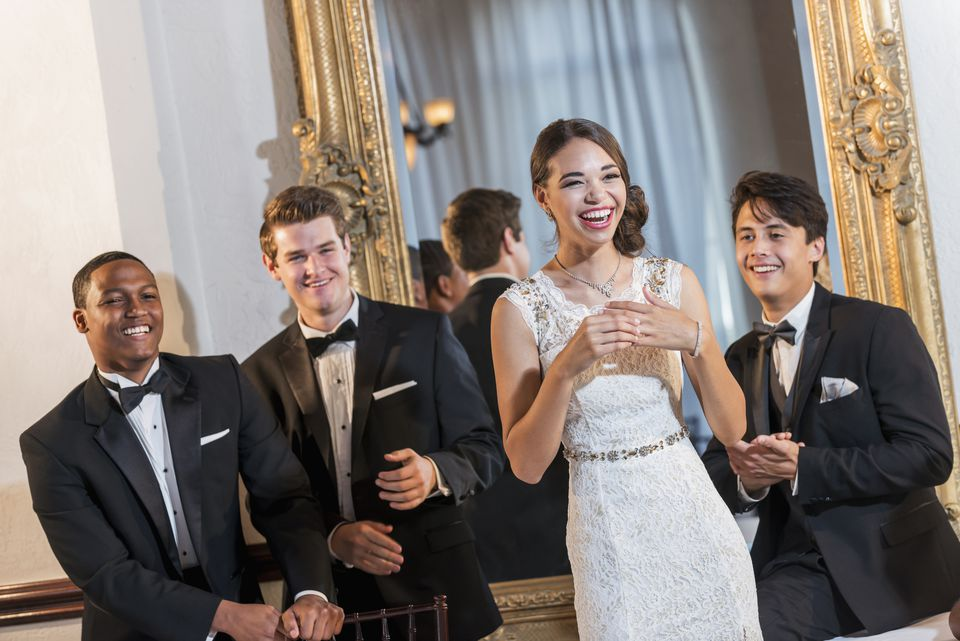 Young woman in gown with three men in tuxedos