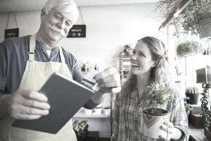 Shop owner using digital tablet credit card reader