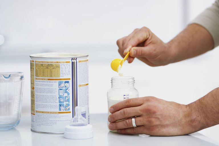Adding power in yellow scoop to bottle containing liquid.