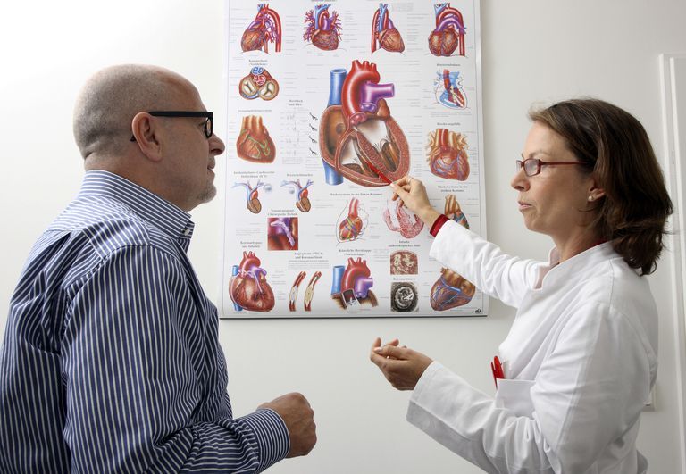 Medical practice, doctor explaining operation and possible diseases of the human heart to a patient
