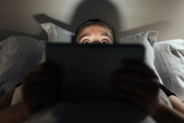 Woman watching scary movie on ipad