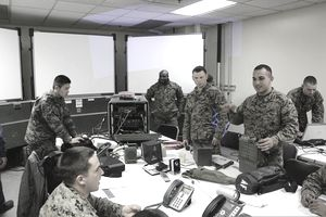 U.S. Marine Corps Lance Cpl. Steven Maldonado, right, a radio operator with Communications Company, Headquarters and Service Battalion, 3rd Marine Division, III Marine Expeditionary Force, explains the PRC-117 and its compatibility with the secure communication controller in the combined operations center during Marine Expeditionary Force Exercise