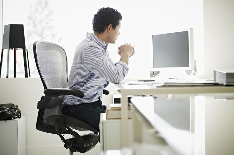 Businessman at desk in high tech startup office.