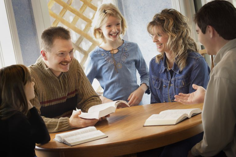 Family reading the Bible together around a table
