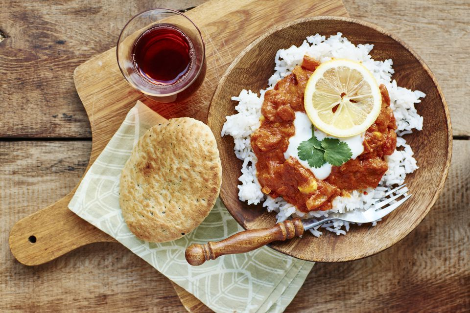 Seitan Tikka Masala on rice with soy yogurt and served with paratha breads and tea
