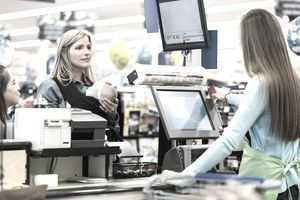 Cashier swiping card for mother holding baby in grocery store