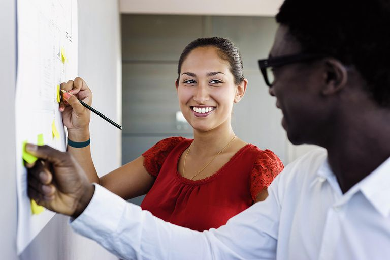 Female and male at work in office writing on board