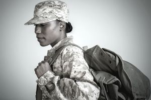 female soldier with rucksack looking down