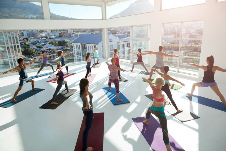 Large yoga class stretching arms out