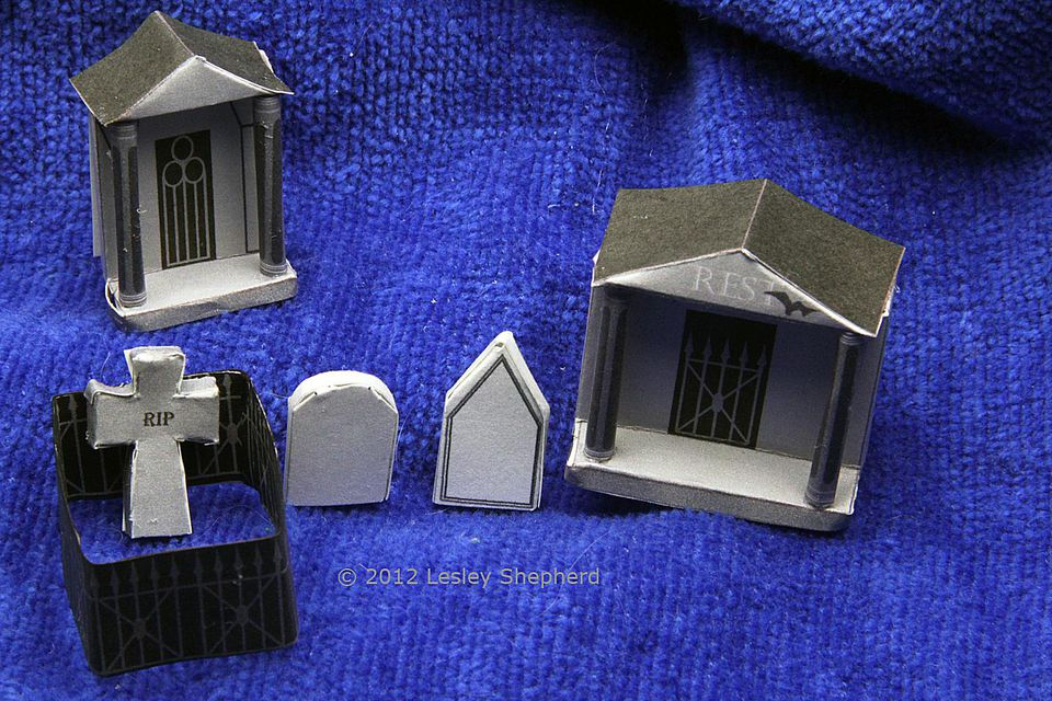 Miniature headstones, fence and mausoleums for a Halloween village graveyard.