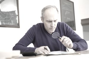 Man looking through magnifying glass at pension document.