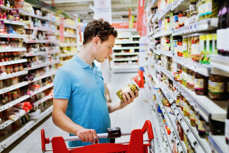 Man looking at jar of olives in grocery store