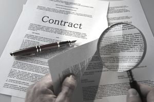 A picture o f a contract with a magnifying glass