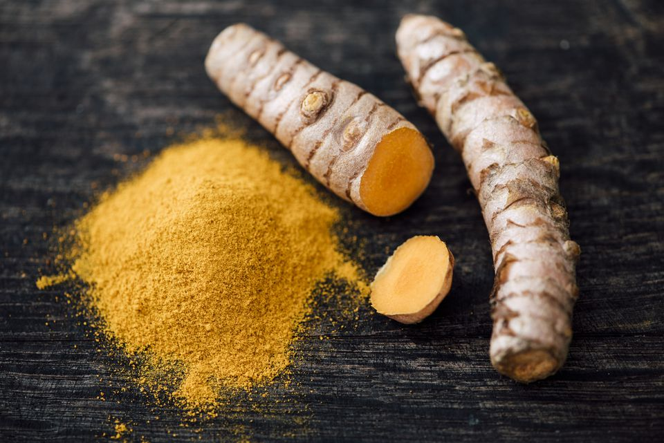 Fresh Curcuma and powder on wood