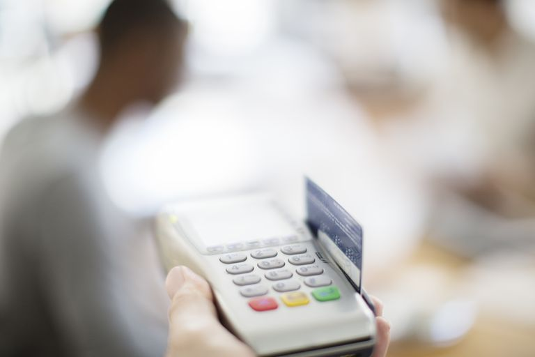 Credit card being swiped through payment machine