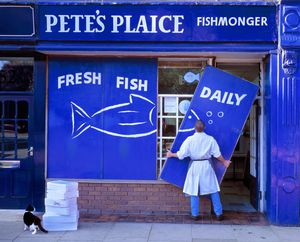 Man hanging sign on fish shop