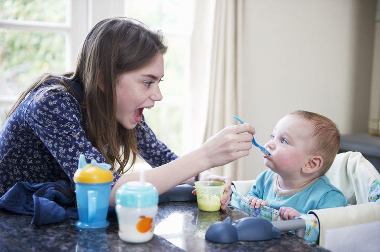 Teen girl feeding baby