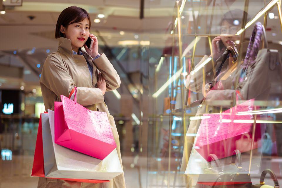 Beautiful young woman using smartphone at shopping mall.