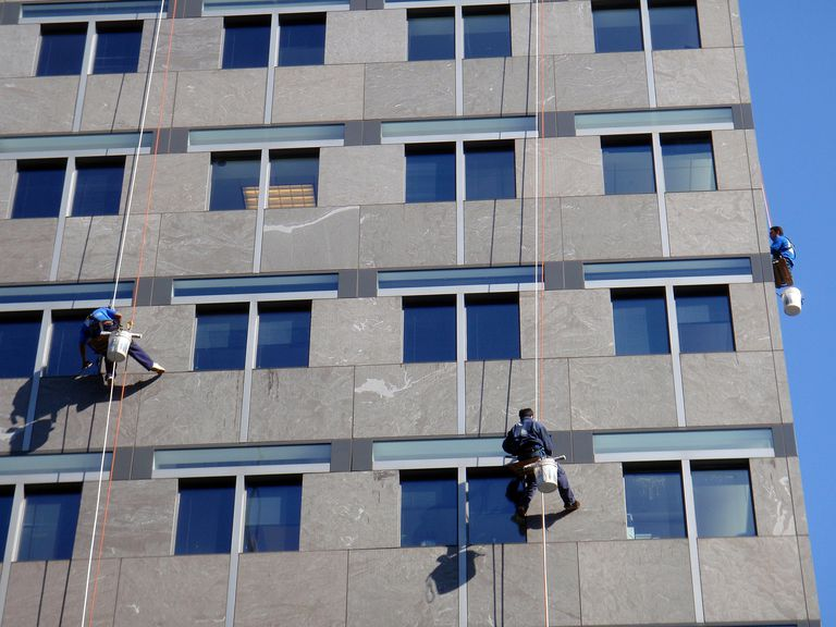 three workers cleaning windows