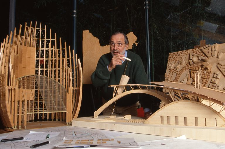middle-aged bearded man in a sweater surrounded by wooden models