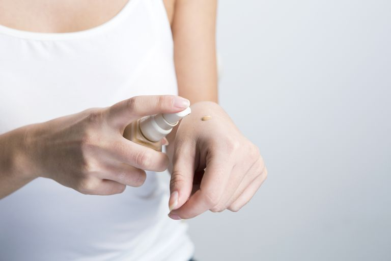 woman applying drop of liquid sheer foundation to back of her hand