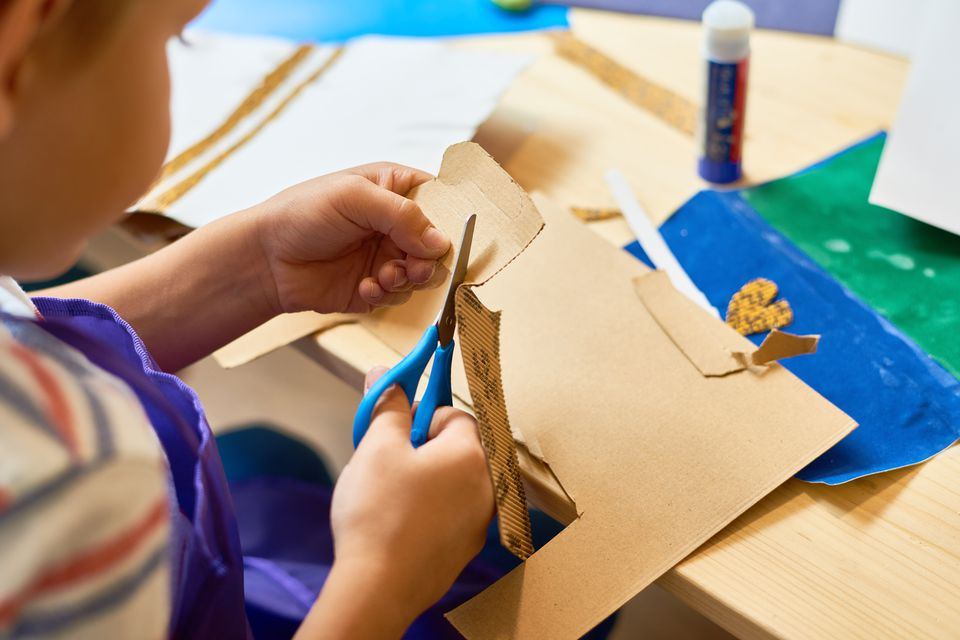 Young boy cutting paper for crafts
