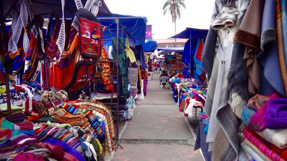 Narrow Pathway Along Market Stalls