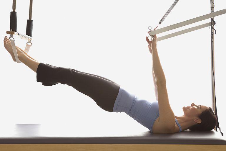 A woman performs a Pilates exercise.