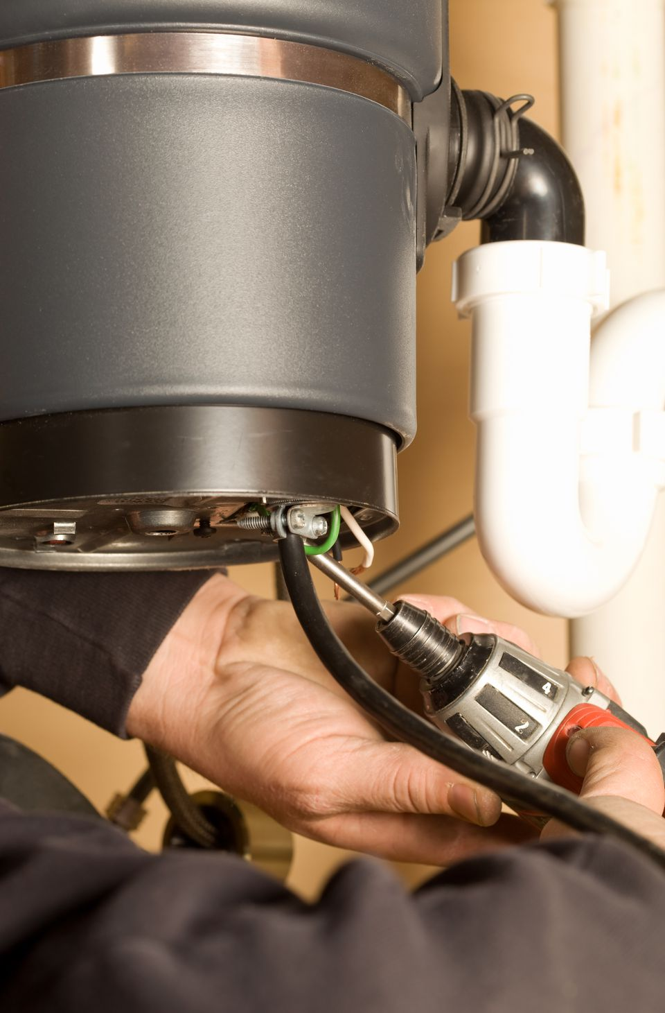 Electrician Wiring a New Kitchen Garbage Disposer