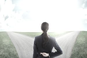 Woman standing looking at two roads representing life insurance options