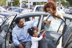 Black family admiring new car
