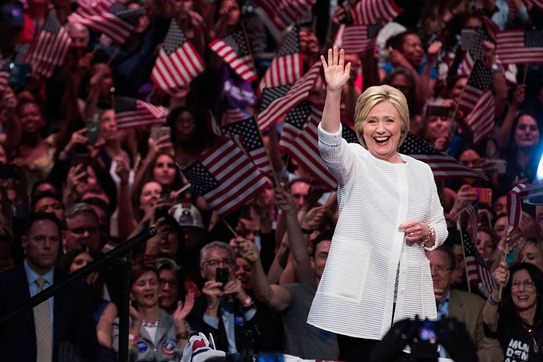 Hillary Clinton waves in front of crowd of people waving U.S. flags