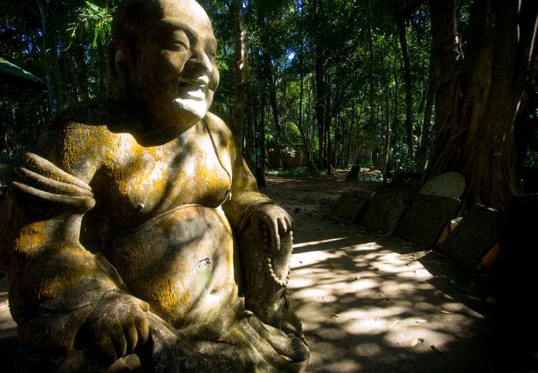 A smiling stone Buddha in the forest outside of Chaya, Thailand.
