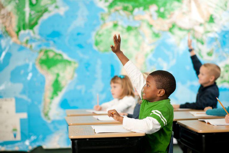 first grade classroom - kids raising hands