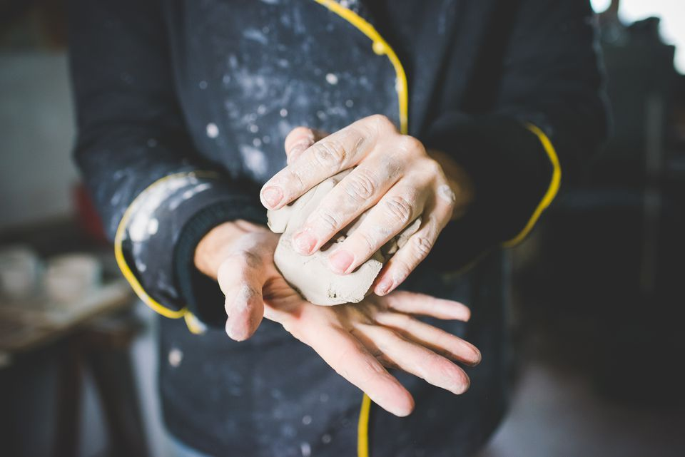 Cropped view of mid adult man squeezing clay in hands
