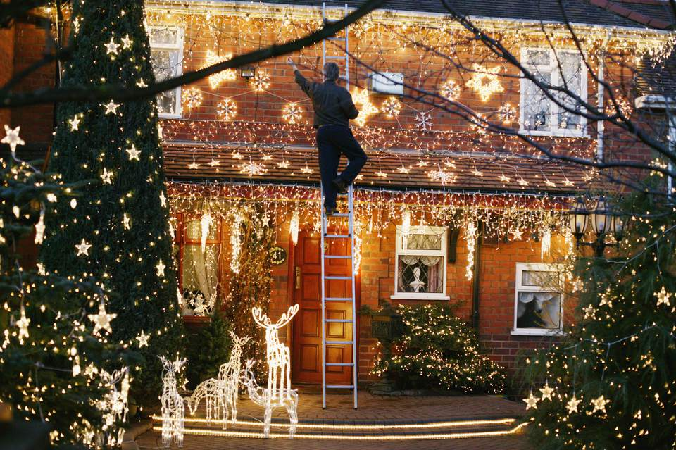 Learn to hang outdoor christmas lights how to hang christmas lights christmas lights in the front garden of a house aloadofball