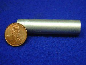 Photograph of the element magnesium, with a penny to indicate size of the sample.