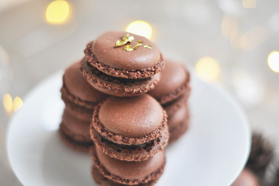 Stack of chocolate macarons on white plate