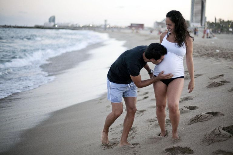 Pregnant couple walking along beach while husband is kissing woman belly.